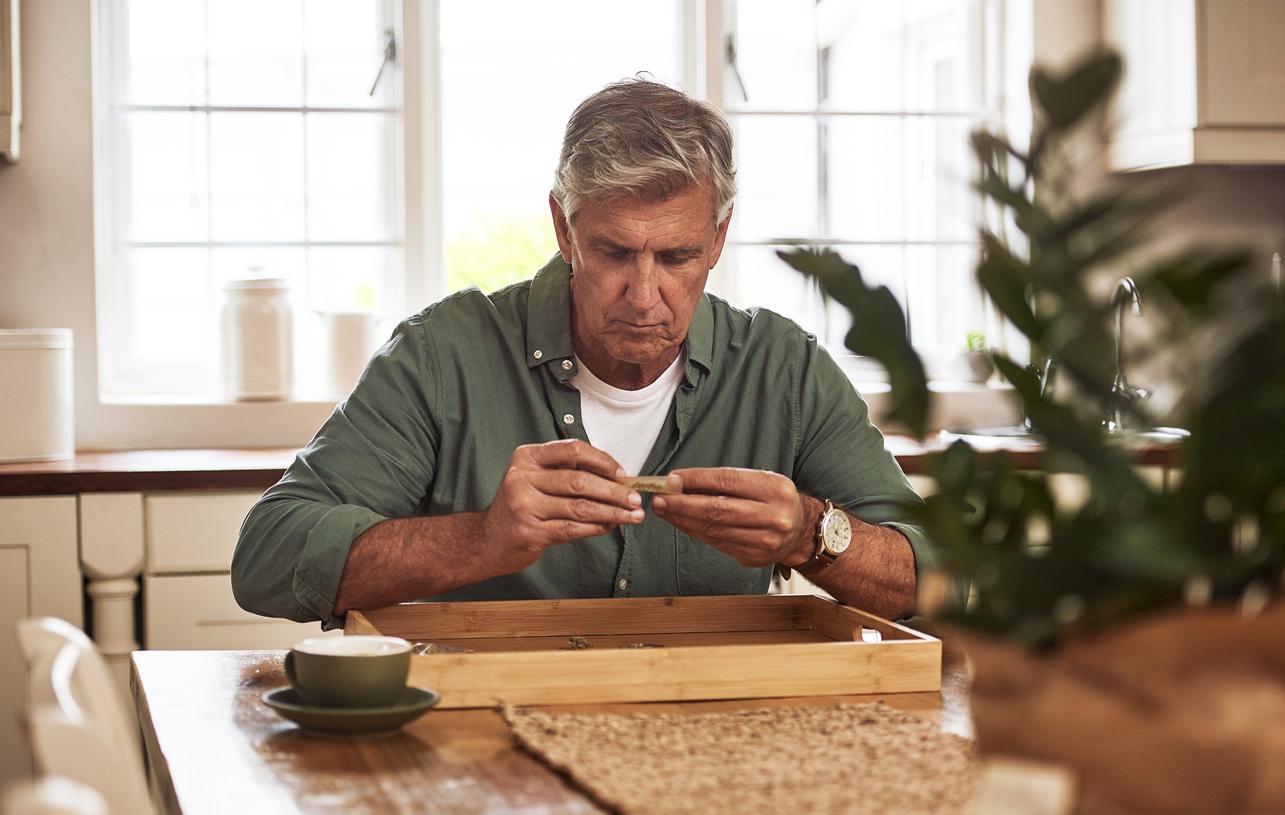Senior man in his kitchen preparing his medical marijuana.